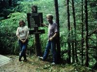 Emmalee Blender and Larry Roberts. Johnsonville sign, Kupreanof, Alaska. July 1996.